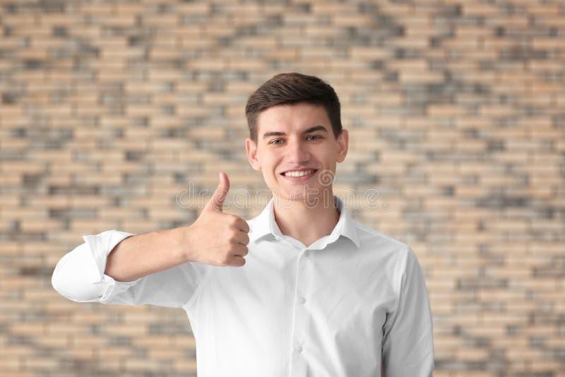 Ritratto del gesto bello del pollice-su di rappresentazione del giovane contro il muro di mattoni immagine stock