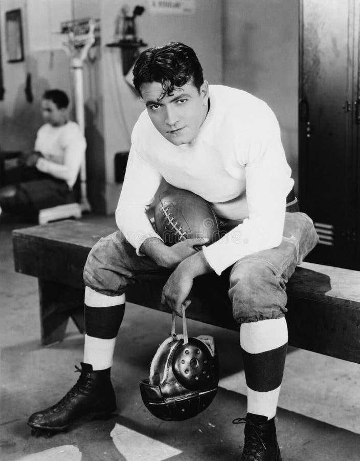 Ritratto del giocatore di football americano nello spogliatoio (tutte le persone rappresentate non sono vivente più lungo e nessu fotografia stock