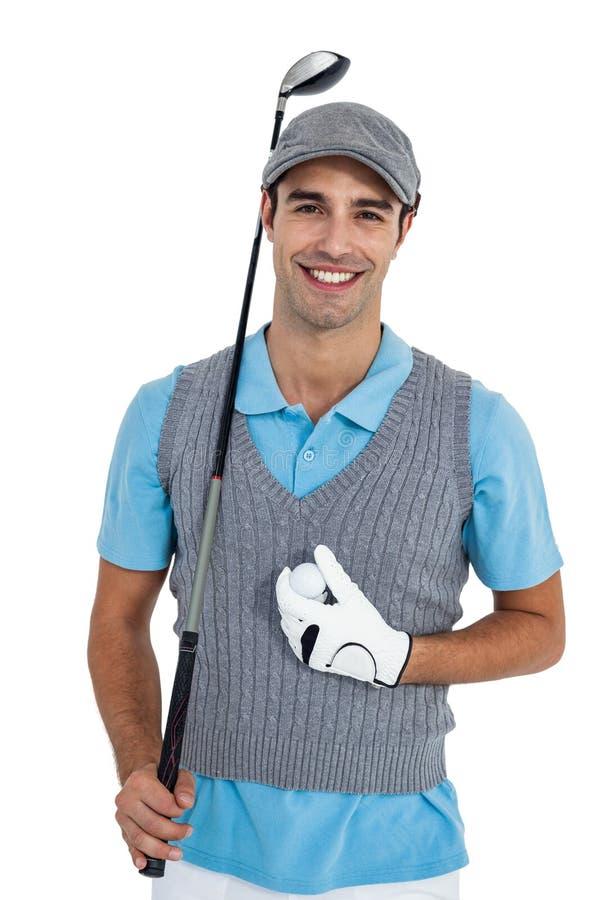 Ritratto del giocatore di golf che sta con la palla da golf ed il club di golf immagini stock