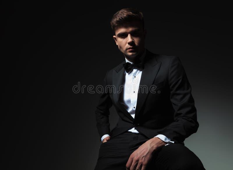 Ritratto del giovane alla moda con la mano nella seduta della tasca immagine stock libera da diritti