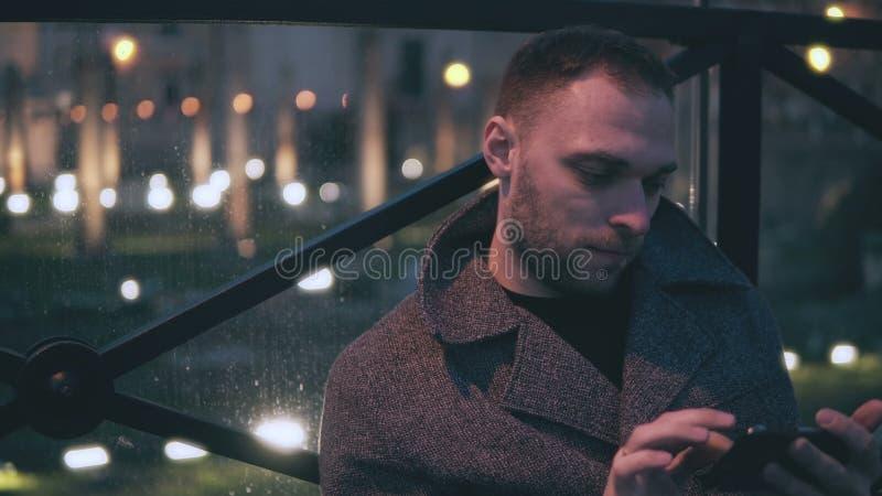 Ritratto del giovane attraente che si siede nella città di sera e nello smartphone di uso Il maschio bello passa in rassegna Inte immagini stock libere da diritti