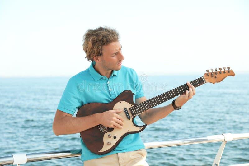 Ritratto del giovane bello con la chitarra fotografia stock libera da diritti