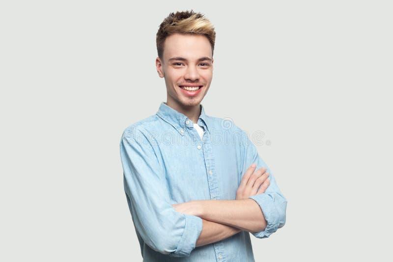 Ritratto del giovane bello soddisfatto felice nella condizione blu-chiaro della camicia con le armi attraversate e nell'esame del fotografie stock libere da diritti