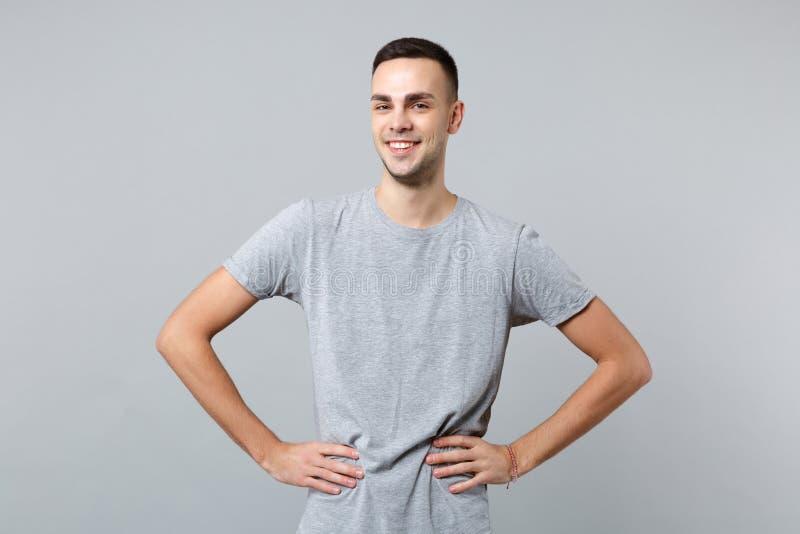 Ritratto del giovane bello sorridente in abbigliamento casual che sta con le armi akimbo sulla vita isolata sulla parete grigia fotografia stock libera da diritti