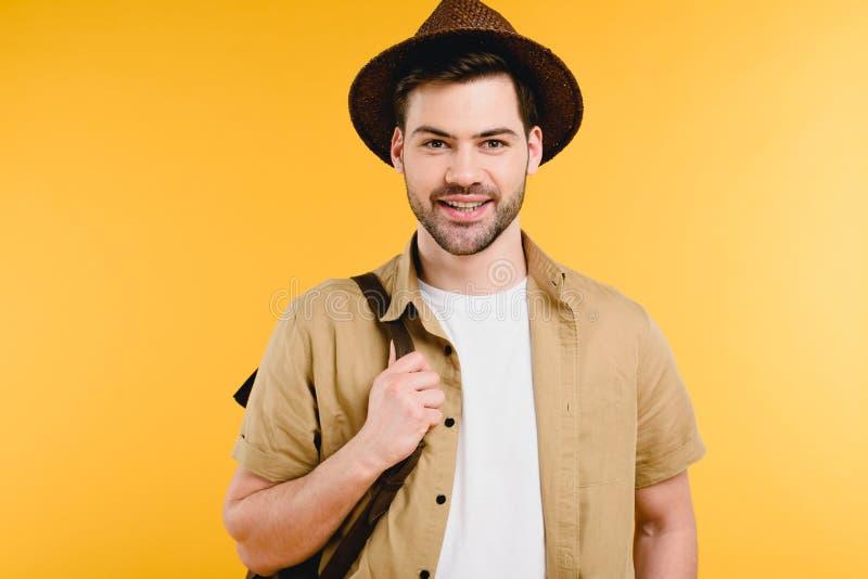 ritratto del giovane bello in zaino della tenuta del cappello e di sorridere alla macchina fotografica immagini stock