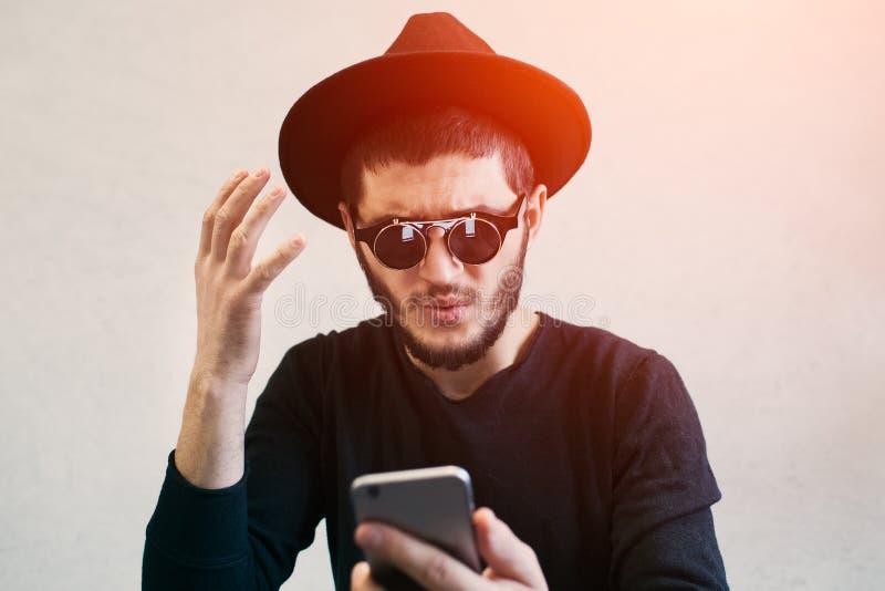 Ritratto del giovane che esamina colpito lo smartphone, vestito in occhiali da sole e cappello neri e d'usi, sopra fondo bianco fotografia stock libera da diritti