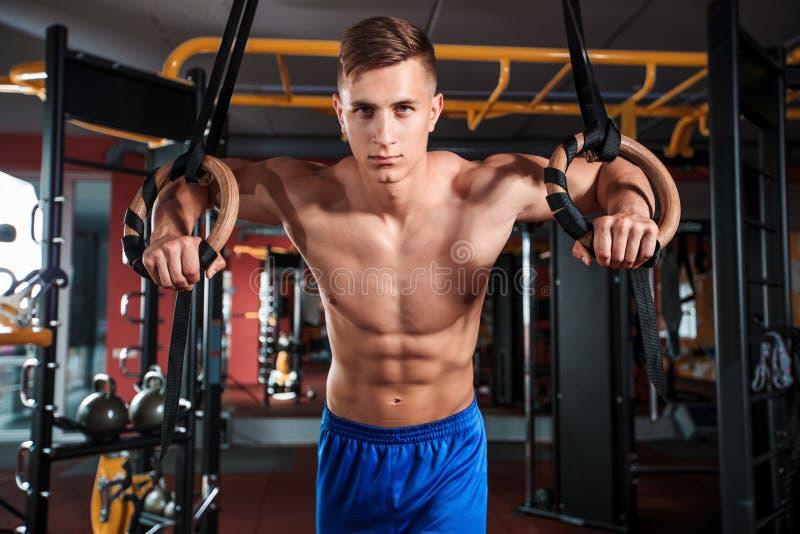 Ritratto del giovane che utilizza gli anelli relativi alla ginnastica mentre esercitandosi nella palestra immagine stock libera da diritti