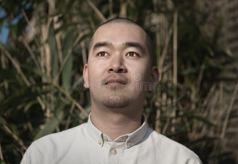 Ritratto del giovane cinese sorridente contro fondo di bambù immagine stock