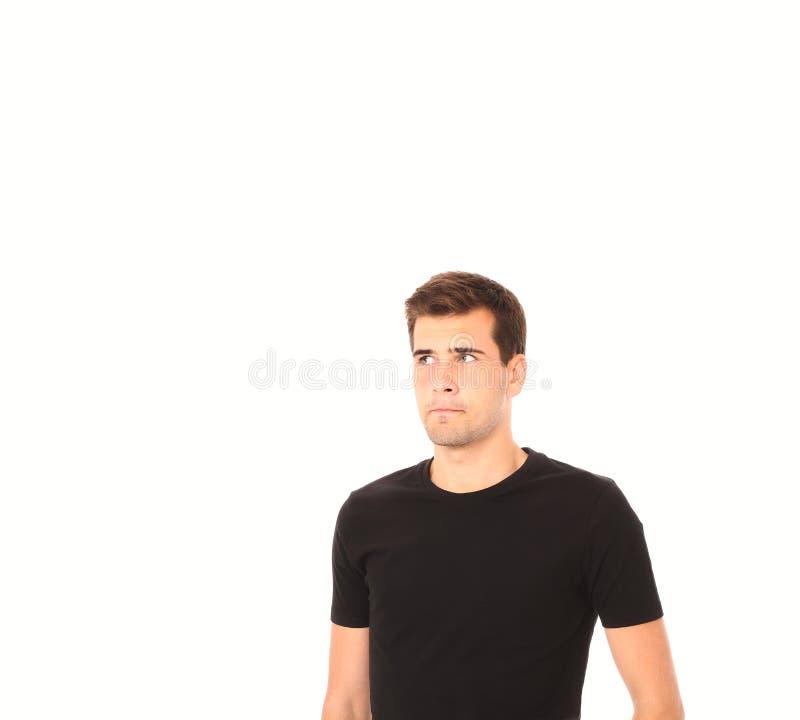 Ritratto del giovane di pensiero astuto in camicia nera isolata su bianco Copi lo spazio Derisione su fotografia stock