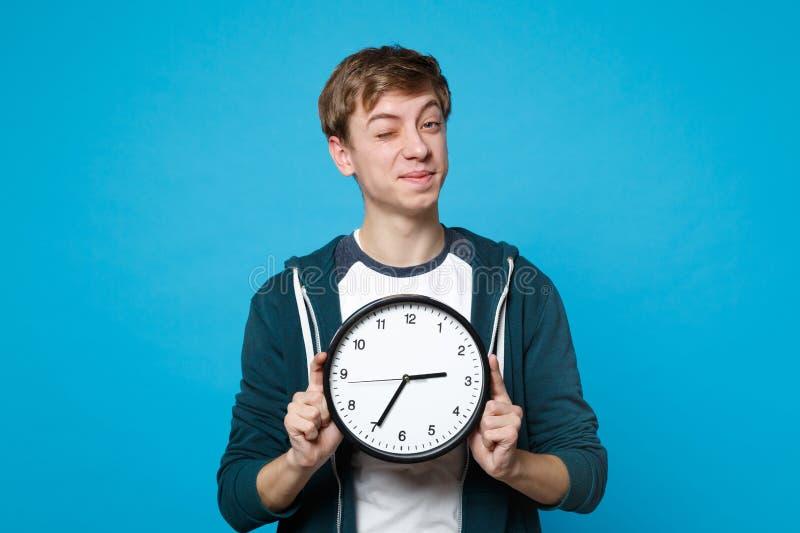 Ritratto del giovane divertente in abbigliamento casual che lampeggia, giudicante orologio rotondo isolato su fondo blu in studio fotografie stock