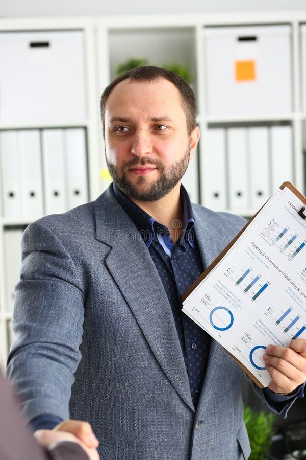 Ritratto del giovane e promettente uomo d'affari in una stretta di mano con un partner commerciale immagine stock