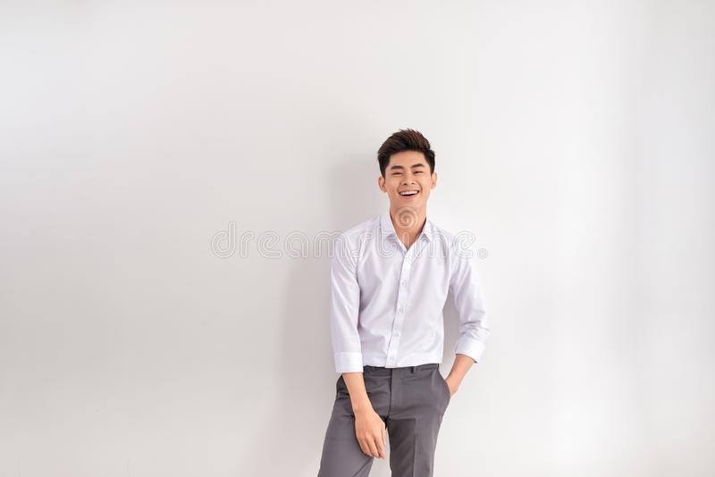 Ritratto del giovane felice che sta contro il fondo bianco fotografie stock
