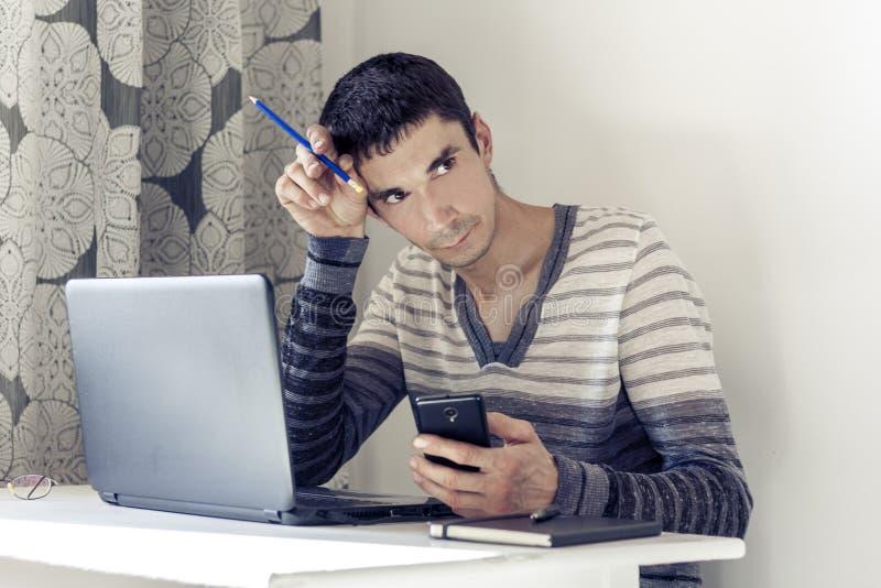 Ritratto del giovane nell'abbigliamento casual sul funzionamento di lavoro sul computer portatile, facendo uso dello smartphone e immagini stock libere da diritti