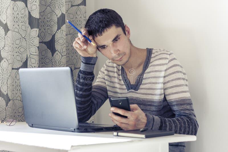 Ritratto del giovane nell'abbigliamento casual sul funzionamento di lavoro sul computer portatile, facendo uso dello smartphone e immagine stock libera da diritti