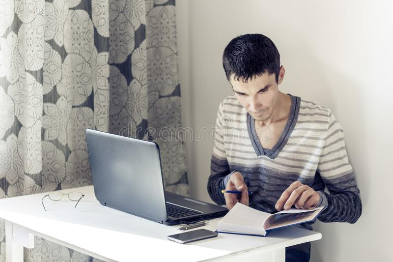 Ritratto del giovane nell'abbigliamento casual sul funzionamento di lavoro sul computer portatile, facente le note in taccuino immagine stock