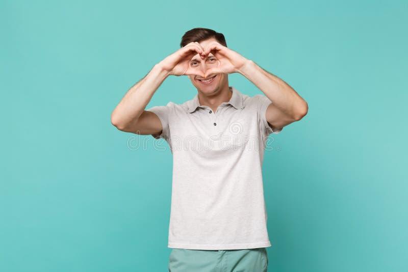 Ritratto del giovane sorridente in abbigliamento casual che mostra il cuore di forma con le mani isolate sulla parete blu del tur fotografia stock