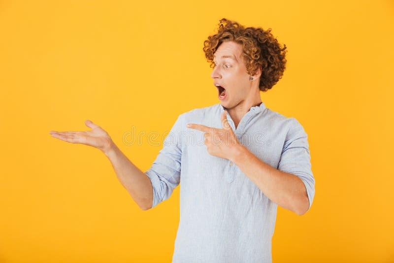 Ritratto del giovane stupito 20s che grida e che tiene copyspace fotografia stock libera da diritti