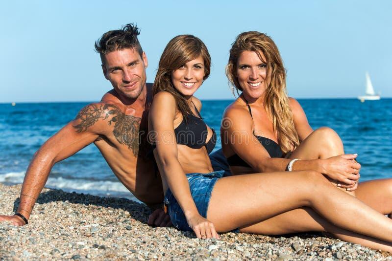 Ritratto del gruppo degli amici che si siedono sulla spiaggia. fotografia stock