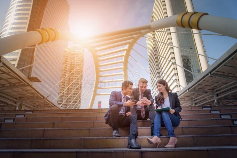 Ritratto del gruppo di affari che si siede alle scale davanti al loro di immagine stock