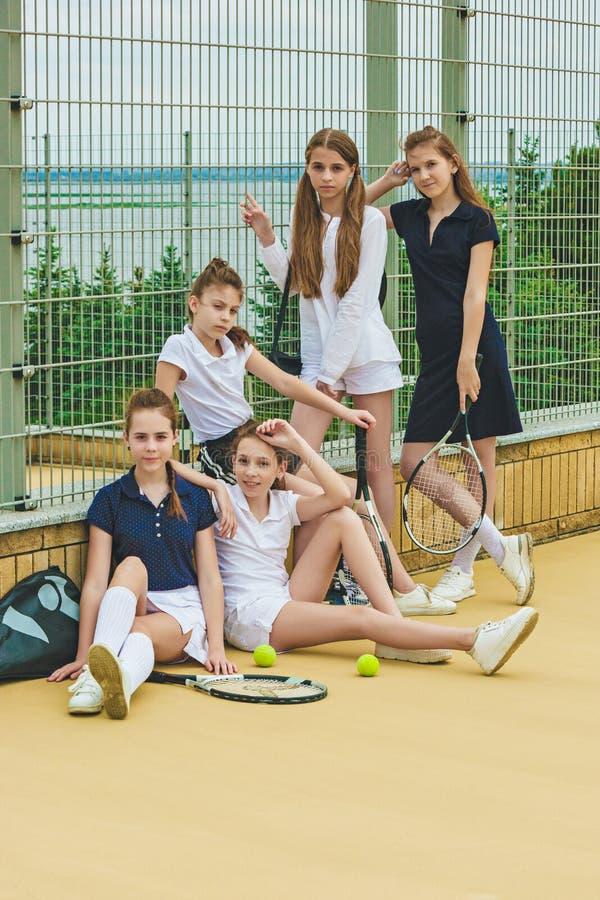 Ritratto del gruppo di ragazze come tennis che tengono la racchetta di tennis contro l'erba verde della corte all'aperto immagini stock