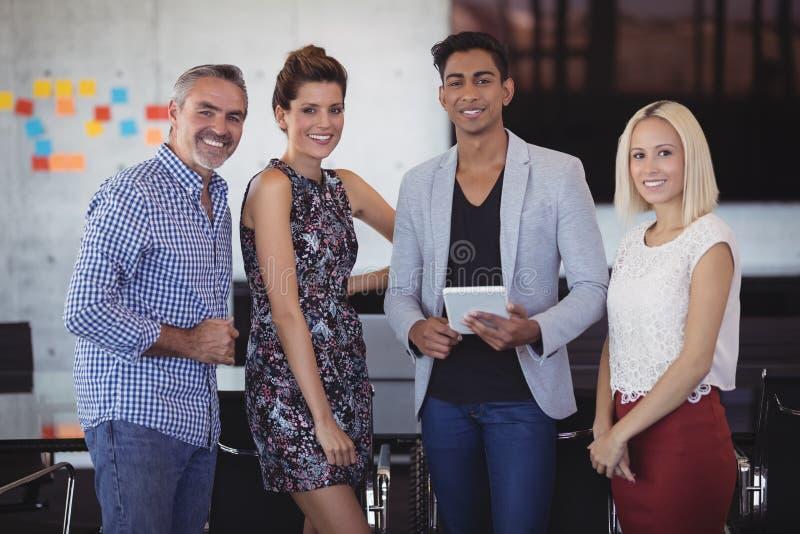 Ritratto del gruppo sorridente di affari che sta all'ufficio creativo fotografie stock libere da diritti