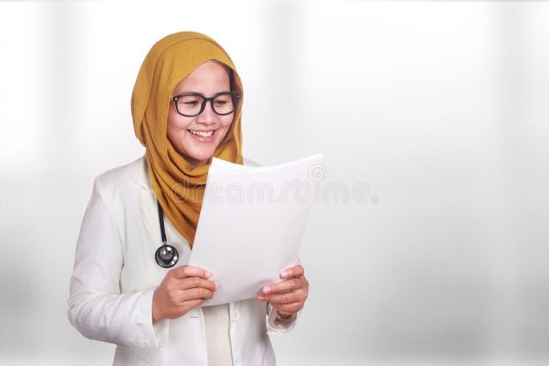 Ritratto del hijab d'uso sorridente felice e della serie della donna musulmana asiatica Carta femminile della perizia medica dell fotografia stock libera da diritti
