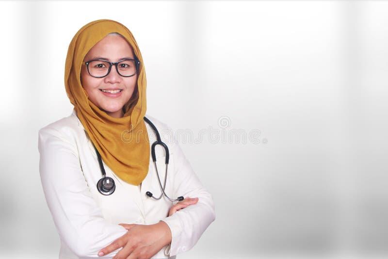 Ritratto del hijab d'uso sorridente felice e della serie della donna musulmana asiatica Medico femminile con le armi attraversate fotografie stock