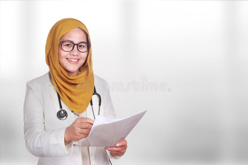 Ritratto del hijab d'uso sorridente felice e della serie della donna musulmana asiatica Medico femminile di fiducia che scrive su immagine stock libera da diritti