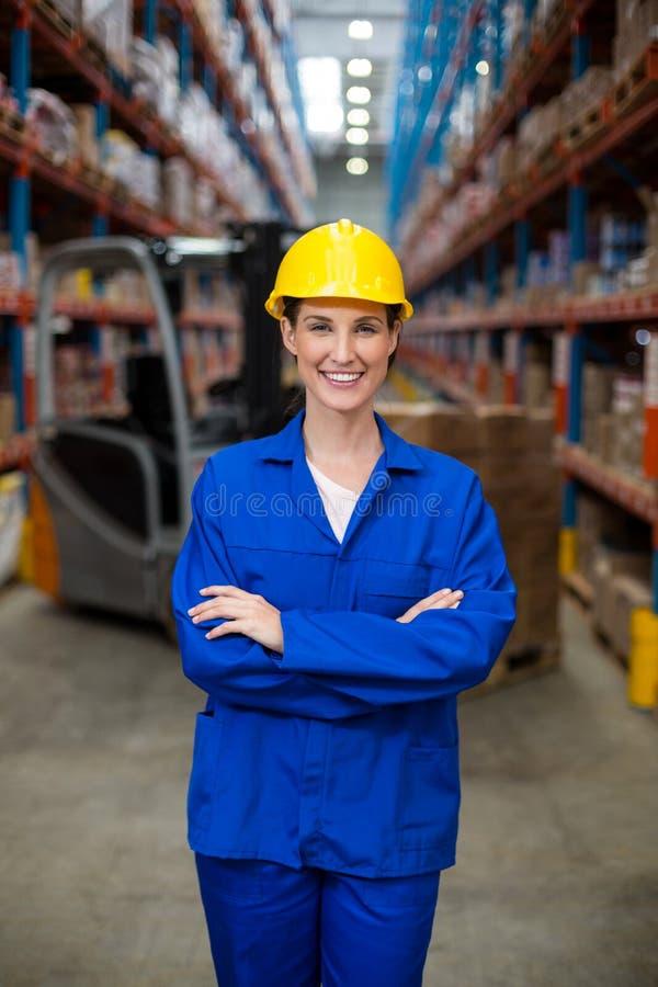 Ritratto del lavoratore femminile del magazzino che sta con le armi attraversate fotografia stock
