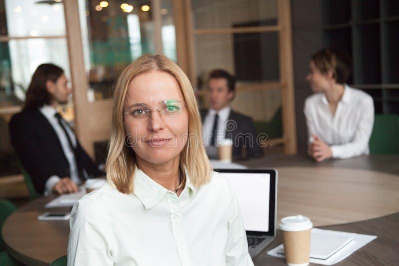 Ritratto del leader della squadra femminile che posa esaminando macchina fotografica fotografia stock