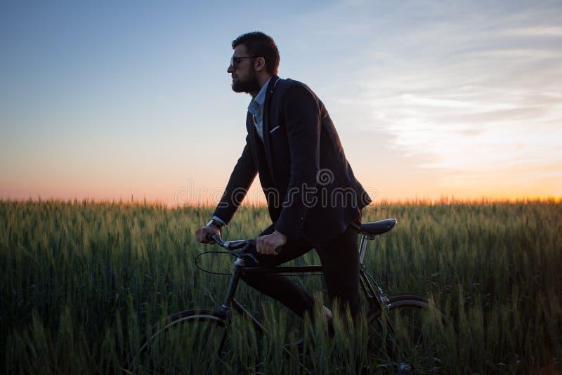 Ritratto del maschio alla moda con la retro bicicletta nel giacimento di grano di estate immagine stock