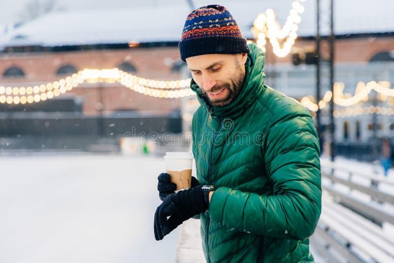 Ritratto del maschio barbuto vestito in vestiti caldi, sguardi all'orologio fotografie stock libere da diritti