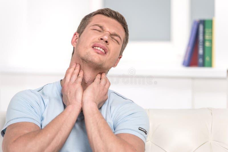 Ritratto del maschio bello con dolore in gola fotografia stock libera da diritti
