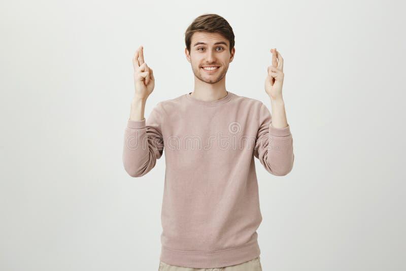 Ritratto del maschio caucasico affascinante con la setola che solleva le mani con le dita attraversate e che sorride, esprimente  immagine stock