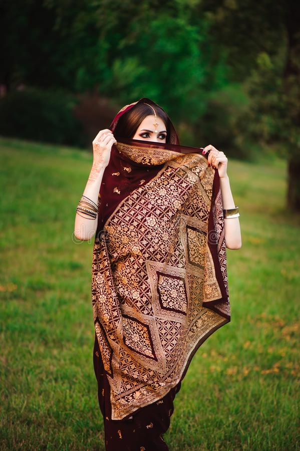 Ritratto del modello indiano di bellezza con trucco luminoso che che nasconde il suo fronte dietro il velo Giovane donna indù con immagini stock libere da diritti