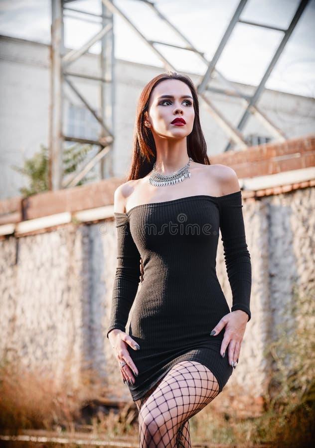 Ritratto del modello informale della bella ragazza del goth in vestito nero e calzamaglia che stanno nella zona industriale fotografia stock