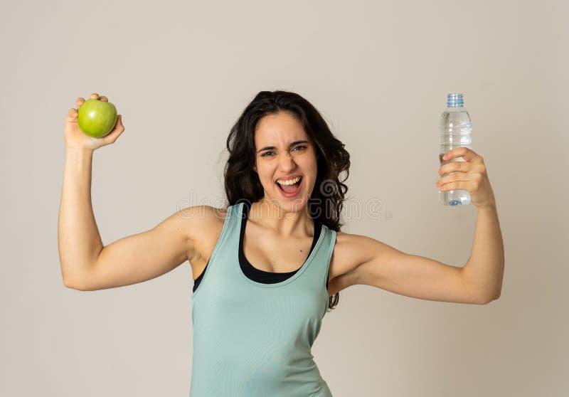 Ritratto del modello latino attraente di forma fisica con la mela ed acqua che ritiene sana ed adatta immagini stock