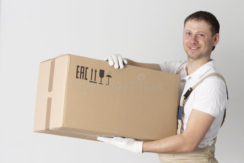 Ritratto del motore con la scatola di cartone in mani su fondo grigio L'uomo di servizi della rilocazione tiene la scatola Carica fotografia stock libera da diritti