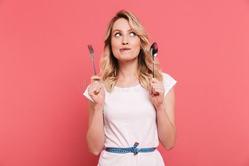 Ritratto del nastro di misurazione d'uso biondo premuroso del corpo della donna 20s intorno al cucchiaio ed alla forchetta della  fotografie stock libere da diritti