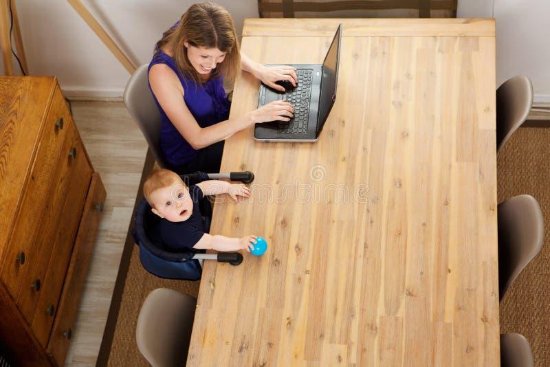 Ritratto del neonato che si siede alla tavola con la donna che per mezzo del computer portatile a casa immagini stock