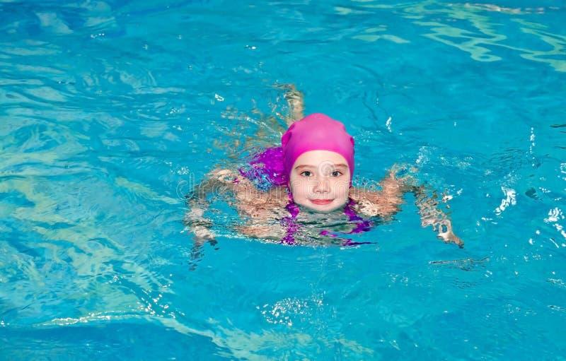 Ritratto del nuotatore sorridente sveglio del bambino della bambina in vestito e cappuccio di nuoto rosa nella cacca di nuoto fotografie stock