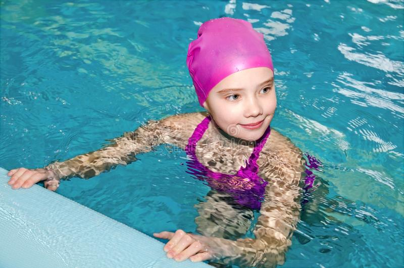 Ritratto del nuotatore sorridente sveglio del bambino della bambina in vestito e cappuccio di nuoto rosa nella piscina fotografia stock libera da diritti
