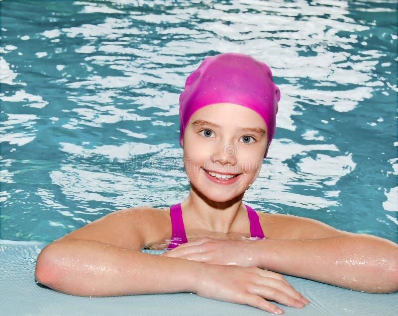 Ritratto del nuotatore sorridente sveglio del bambino della bambina in vestito e cappuccio di nuoto rosa nella piscina fotografie stock libere da diritti