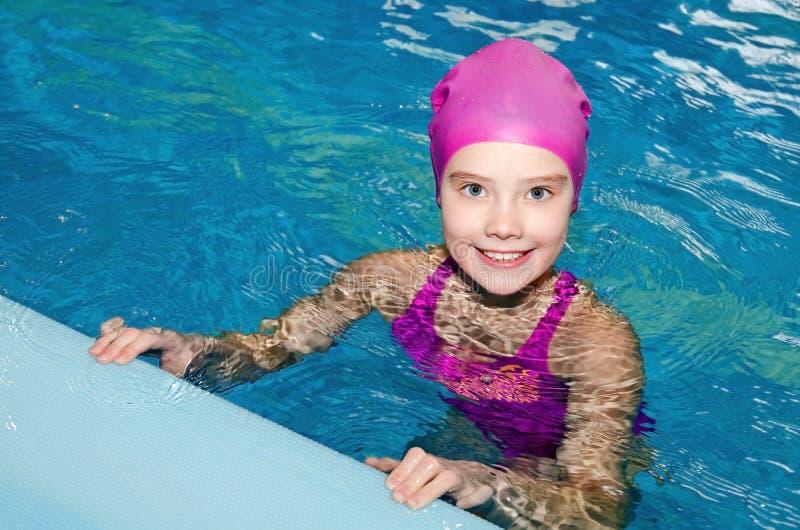 Ritratto del nuotatore sorridente sveglio del bambino della bambina in vestito e cappuccio di nuoto rosa nella piscina fotografia stock