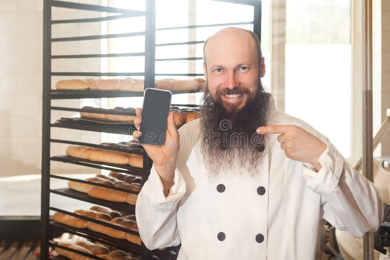 Ritratto del panettiere adulto soddisfatto dell'uomo d'affari con la barba nella condizione uniforme bianca nel forno e nell'ordi immagine stock