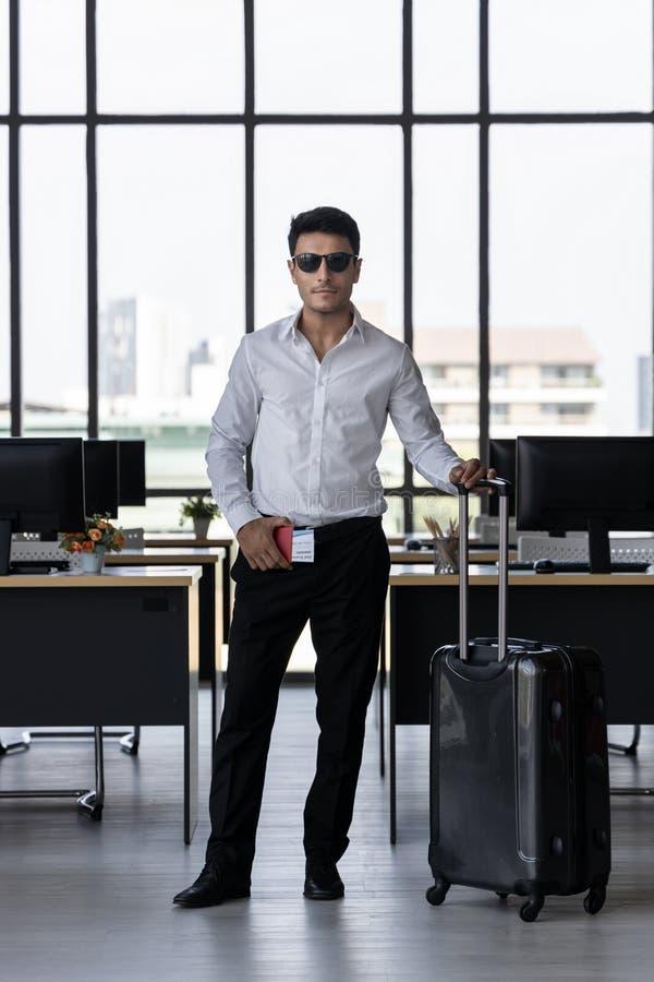 Ritratto del passaporto allegro della tenuta dell'uomo di affari e bagagli in posto di lavoro dell'ufficio Concetto di vacanze es fotografia stock