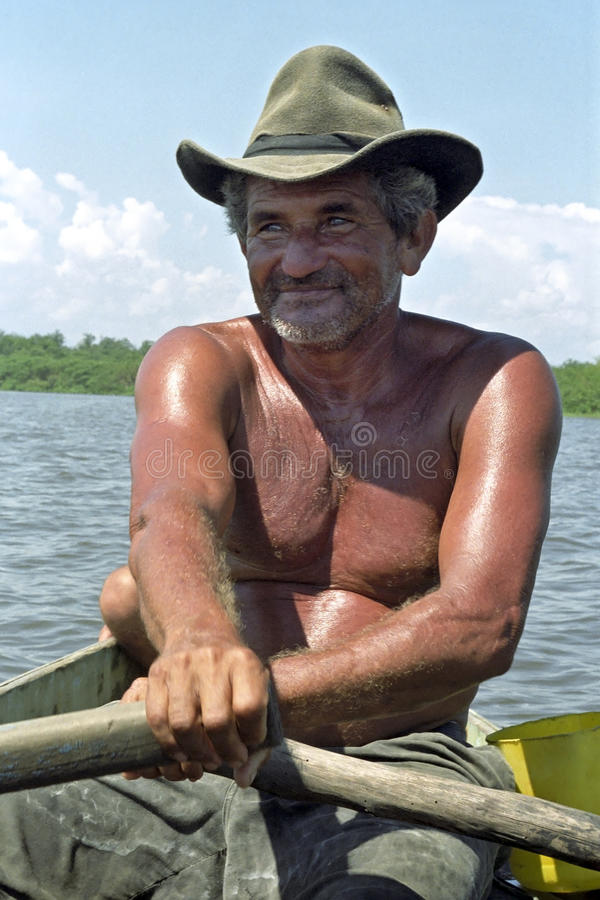 Ritratto del pescatore senior che rema la sua barca fotografia stock libera da diritti