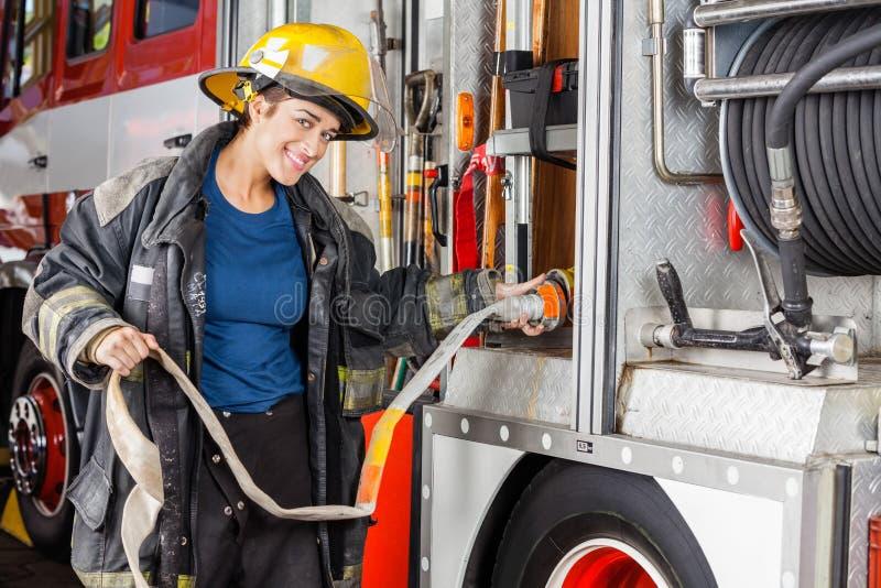 Ritratto del pompiere felice Adjusting Hose In fotografie stock libere da diritti