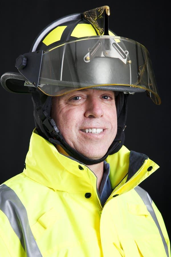 Ritratto del pompiere sul nero fotografia stock