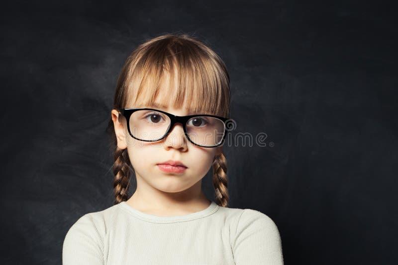 Ritratto del primo piano del bambino pensieroso Ragazza sveglia del bambino sul fondo dell'aula della scuola fotografie stock libere da diritti